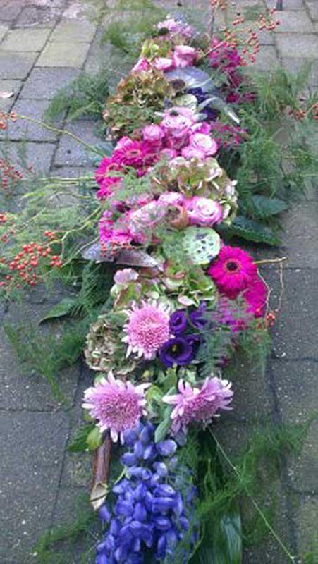 kistbedekking-met-lila-roos-en-gebera-en-rozebottels